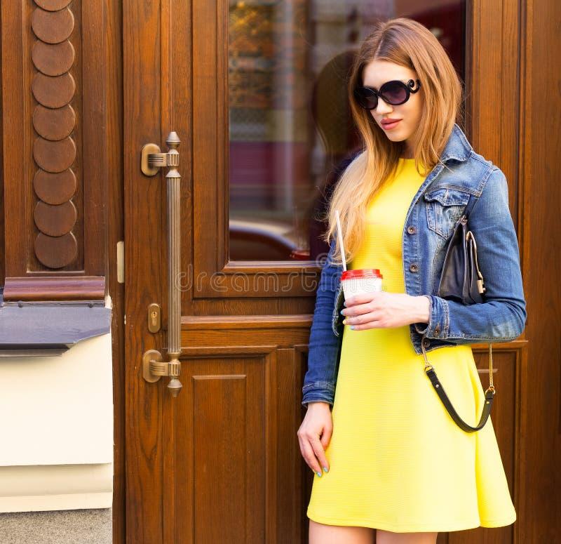 Stående En flicka i solglasögon, en härlig gul sommarklänning och ett grov bomullstvillomslag kommer ut ur dörrar Barns kläder royaltyfri foto