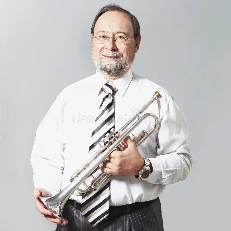 Stående erfaren lärare av musik med en trumpet royaltyfri foto