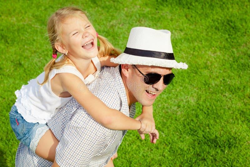 Stående ett fader- och dottersammanträde på gräset på dagen t arkivfoton