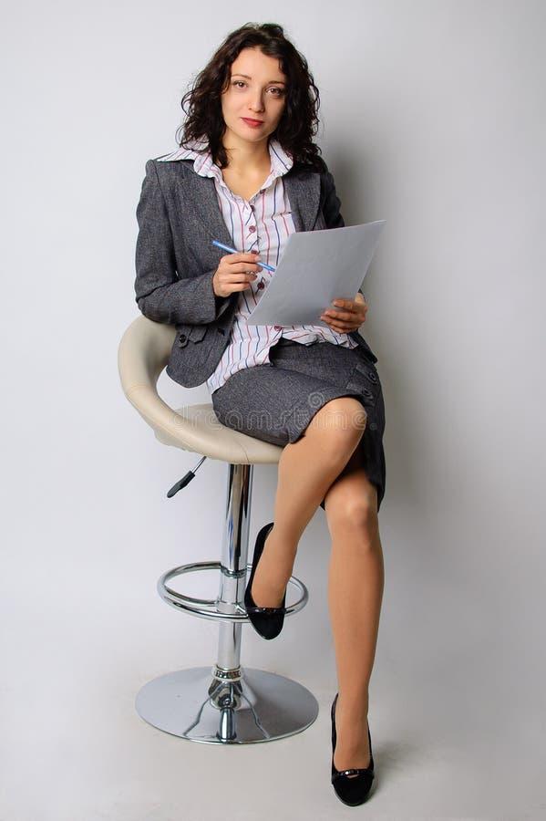 Stående för affärskvinna Brunetten går på en hög stol Han rymmer ett ark av papper och en kulspetspenna i hans arkivbild