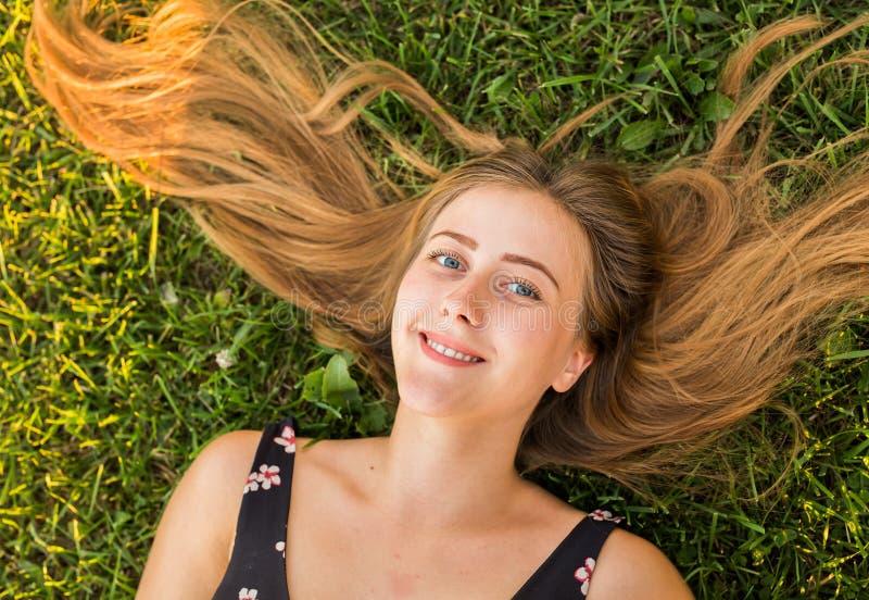 Stående för bästa sikt av en nätt ung kvinna som kopplar av på en gräsnärbild royaltyfri fotografi