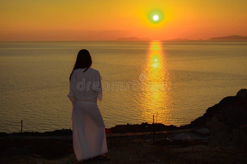 Stående för bakre sikt av en kvinna i en vit klänning i de ljusa strålarna av solnedgången i Santorini arkivfoto