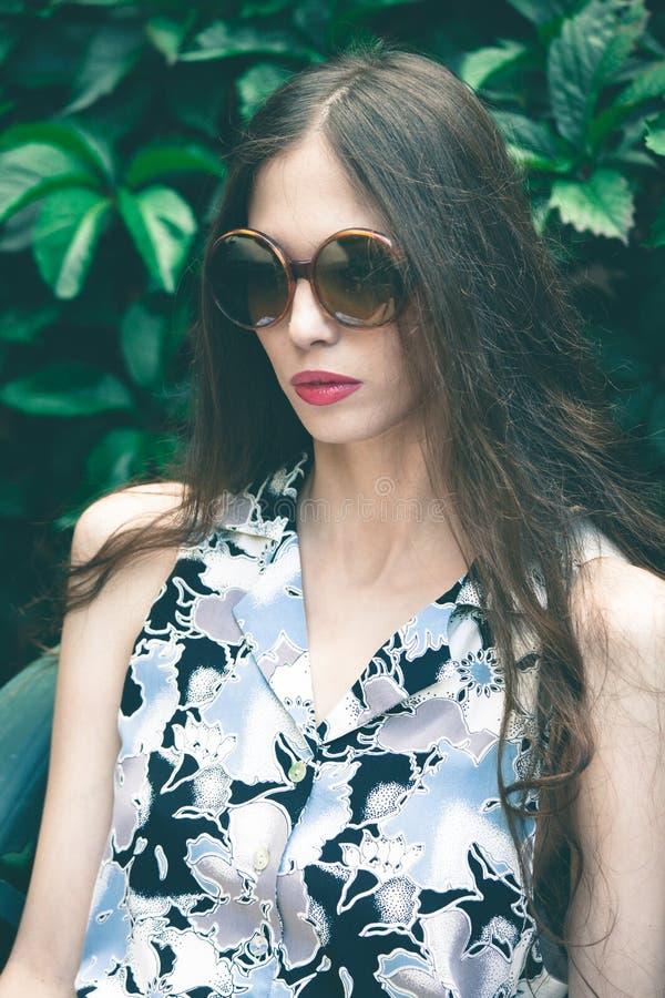 Stående för barnmodekvinna med solglasögon i trädgård royaltyfri foto