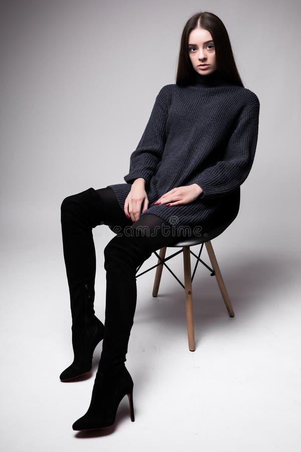 Stående för högt mode av ung sittung för elegant kvinna på stolsvartkläder som isoleras på vit bakgrund arkivbilder