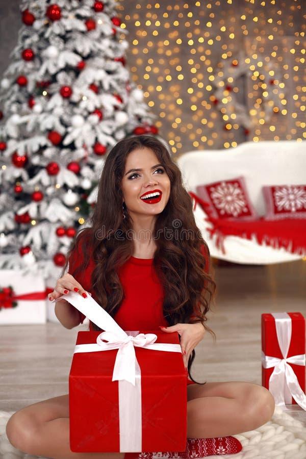 Stående för julflickavinter Ask för gåva för härlig santa kvinna öppen närvarande Lycklig skratta brunett i rött med långt sitta  fotografering för bildbyråer