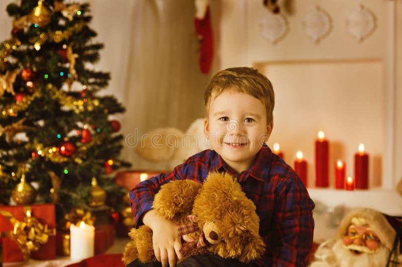 Stående för julungepojke med den närvarande gåvan Toy In Xmas Room royaltyfri foto