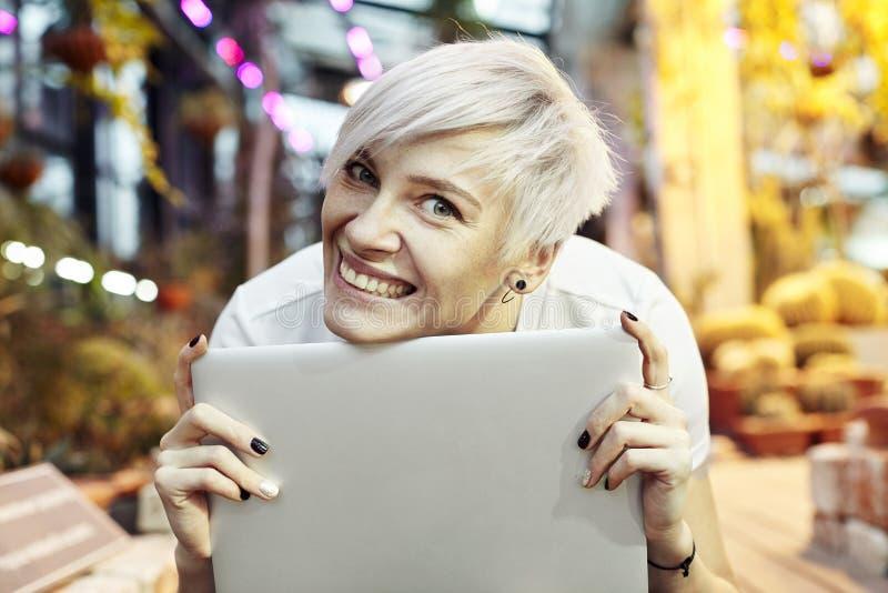 Stående för närbild för kort hår för härlig hipsterkvinna som blond ler och rymmer den bärbara datoren Solig dag i en parkera ell arkivbild