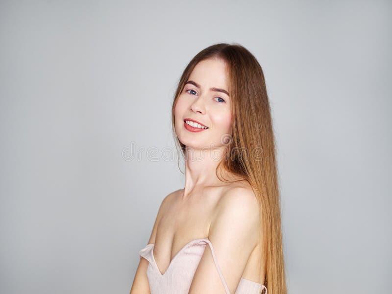 Stående för naturligt ljus av den unga härliga blonda kvinnan med långt hår i tappningklänning som ler se kameran över grå väggba royaltyfri foto