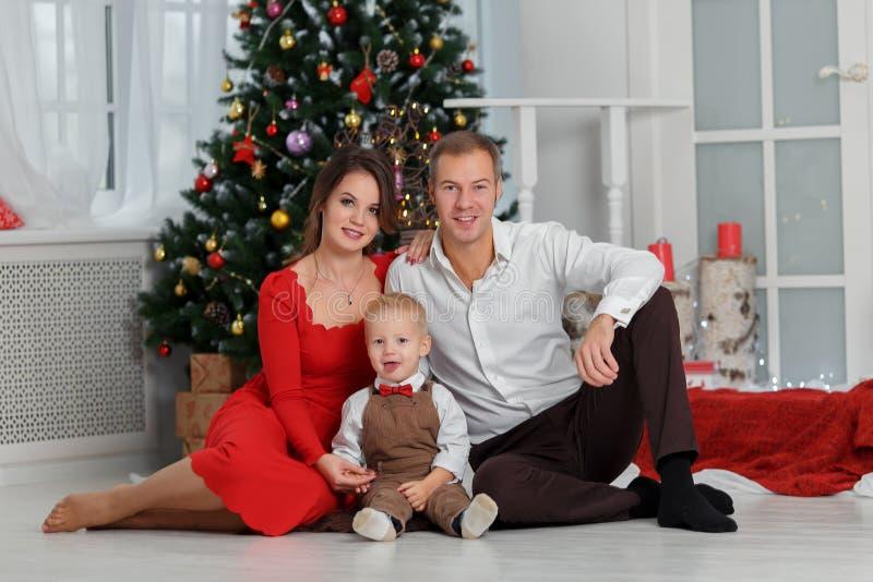 Stående för nytt år och julav den unga familjen i klassisk kläder arkivbild