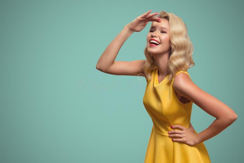 Stående för popkonst av att le den härliga kvinnan mot blå backgro fotografering för bildbyråer