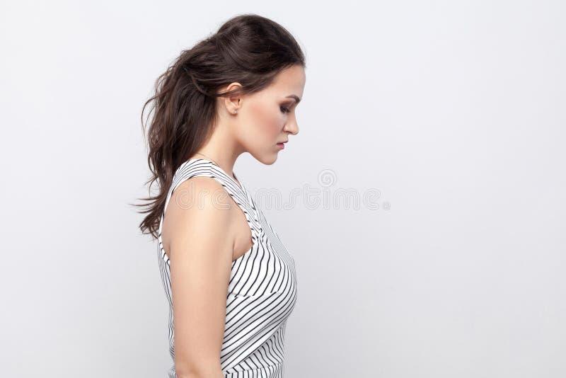 Stående för profilsidosikt av den ledsna härliga unga brunettkvinnan med makeup och det randiga huvudet för klänninganseendeinneh fotografering för bildbyråer