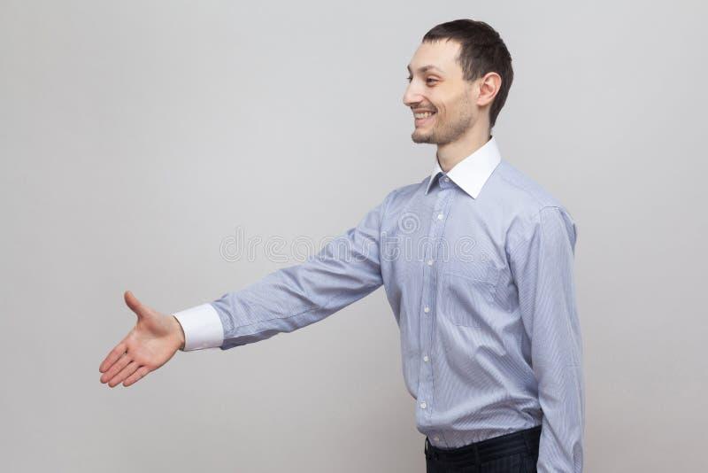 Stående för profilsidosikt av den lyckliga stiliga borstaffärsmannen i klassiskt ljus - blått skjortaanseende som ger handskaknin arkivfoto