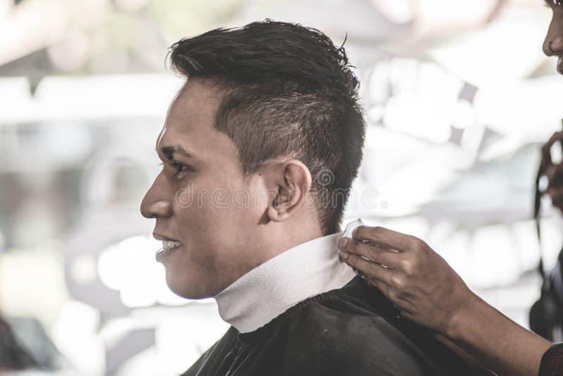 Stående för sidosikt av den attraktiva asiatiska mannen som har hans hals som täcker vid den vita halsräkningen royaltyfria bilder