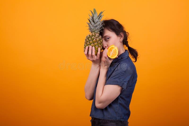 Stående för sidosikt av den härliga unga kvinnan som rymmer den smakliga ananasen och apelsinen i studio över gul bakgrund arkivfoton
