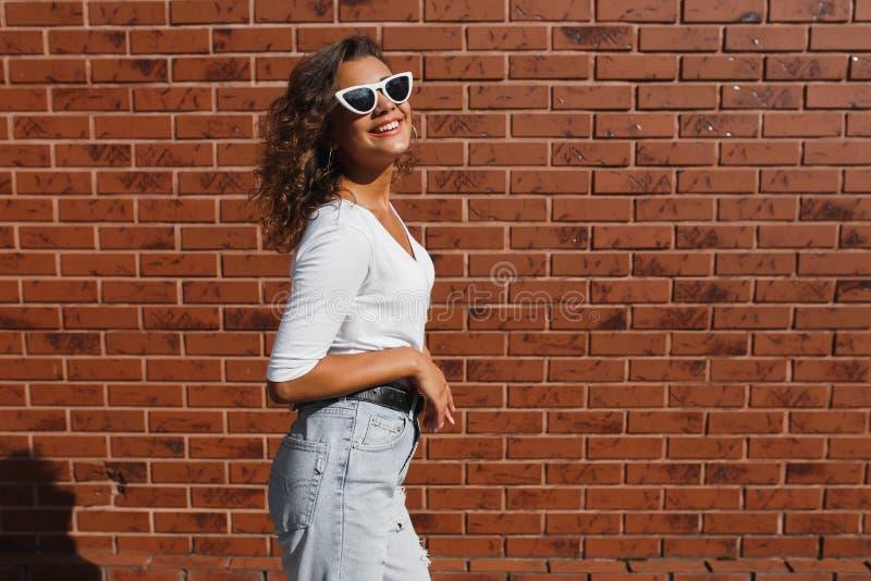 Stående för sidosikt av den unga härliga lyckliga kvinnan i tillfällig torkduk mot tegelstenväggen arkivbilder