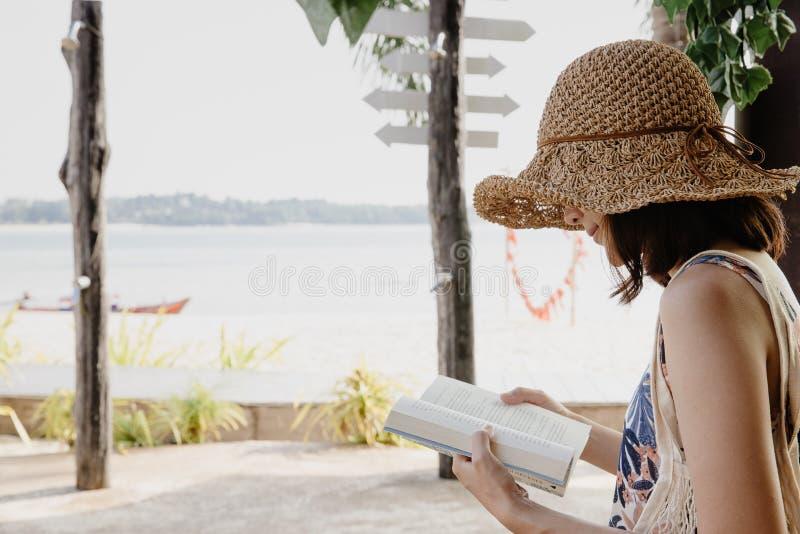 St?ende f?r sidosikt av en lycklig kvinna som l?ser en bok p? stranden i sommarsemester royaltyfri fotografi