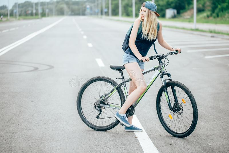 Stående för sidosikt av en ung härlig kvinnaridning på cykeln i stadsgata royaltyfri foto