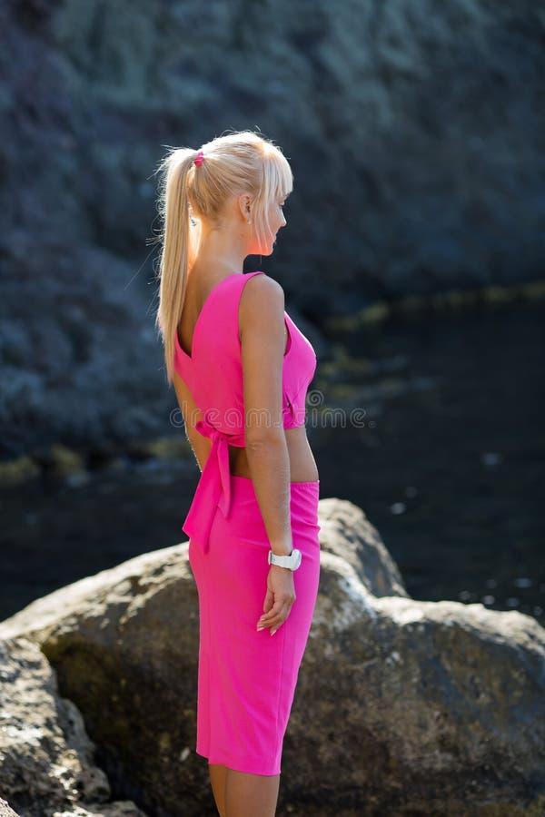 Stående för sidosikt av kvinnan i rosa överkant och kjolen mot den naturliga steniga klippan arkivbild