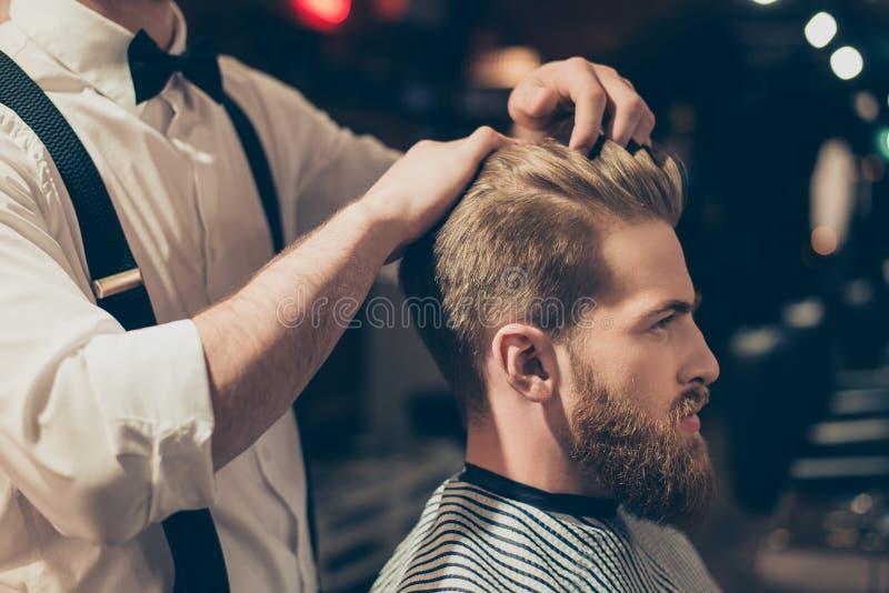 Stående för sikt för profilsidoslut övre av den stiliga virila macho mannen som har hans hår att klippas i frisersalong Begrepp f arkivbilder