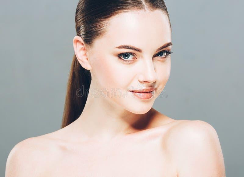 Stående för skönhetkvinnaframsida Härlig brunnsortmodellflicka med perfekt ny ren hud Grå färgbakgrund royaltyfri foto