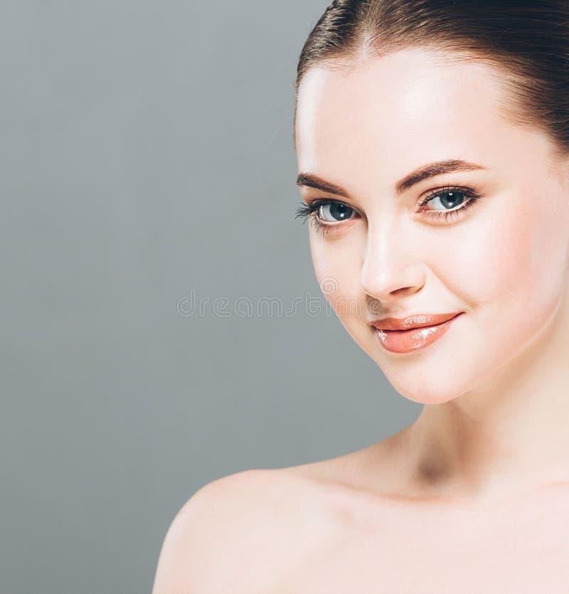 Stående för skönhetkvinnaframsida Härlig brunnsortmodellflicka med perfekt ny ren hud Grå färgbakgrund royaltyfri fotografi