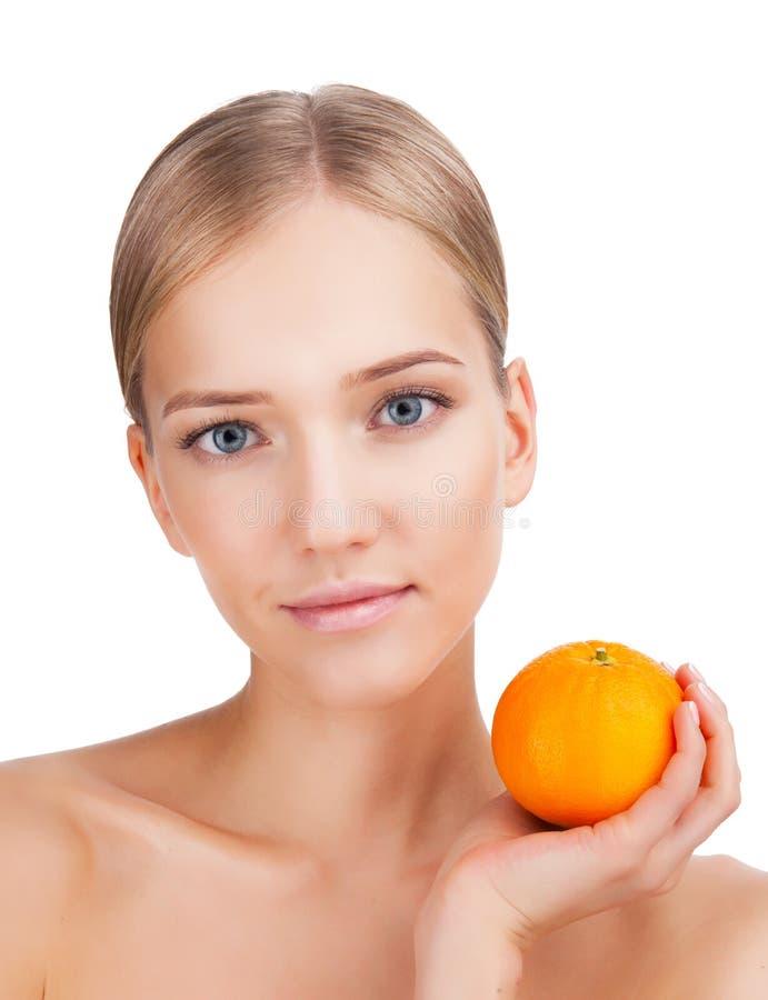 Stående för skönhetkvinnaframsida med apelsinen i hennes hand Begrepp för hudomsorg på en vit bakgrund royaltyfri bild