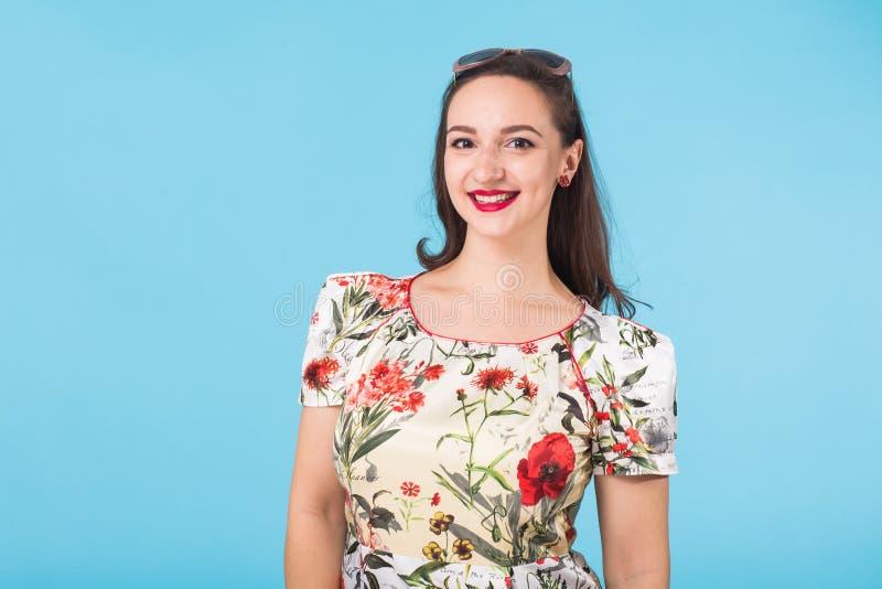 stående för skönhetmodekvinnlig Le den unga kvinnan på blå väggbakgrund arkivfoton