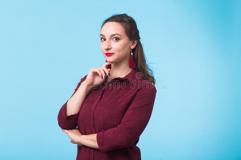 stående för skönhetmodekvinnlig Le den unga kvinnan på blå väggbakgrund arkivfoto