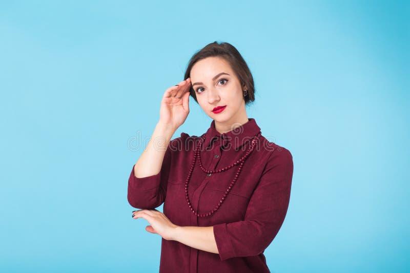 stående för skönhetmodekvinnlig Le den unga kvinnan på blå väggbakgrund royaltyfria foton