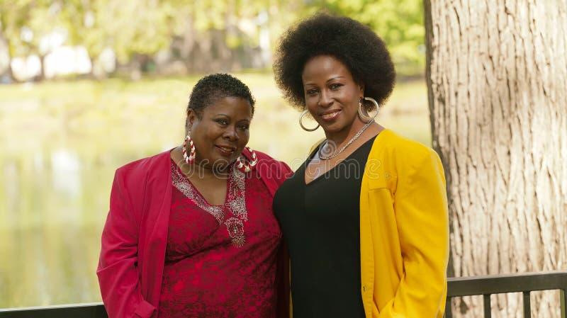 Stående för två röd guling för äldre svarta kvinnor utomhus- royaltyfri bild