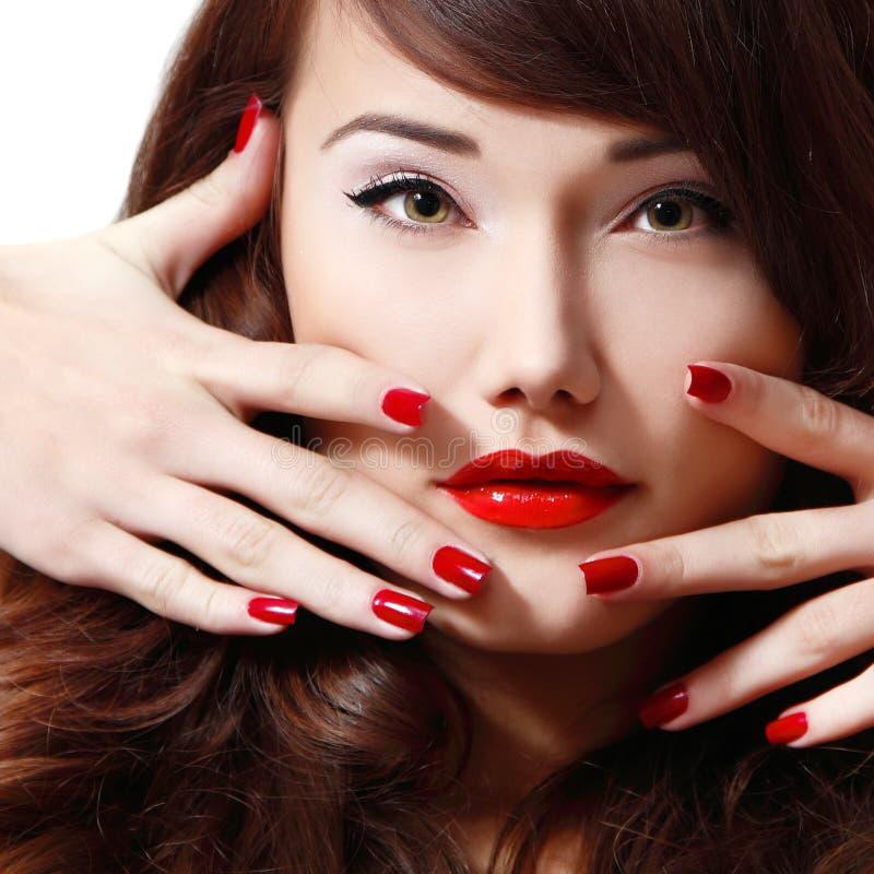 Stående för ung kvinna med långt hår, röd läppstift och manikyr royaltyfri bild