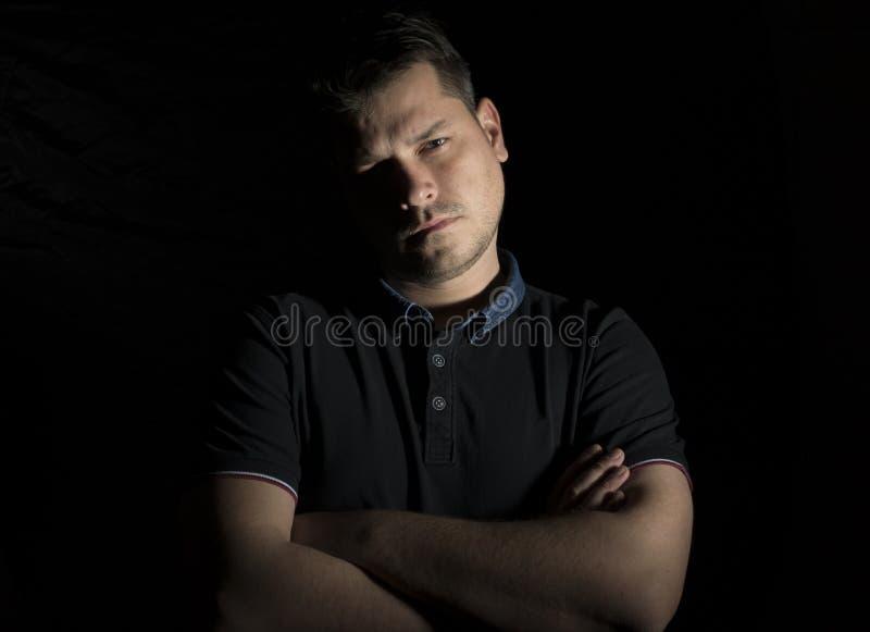 Stående för ung man som isoleras på svart arkivfoton