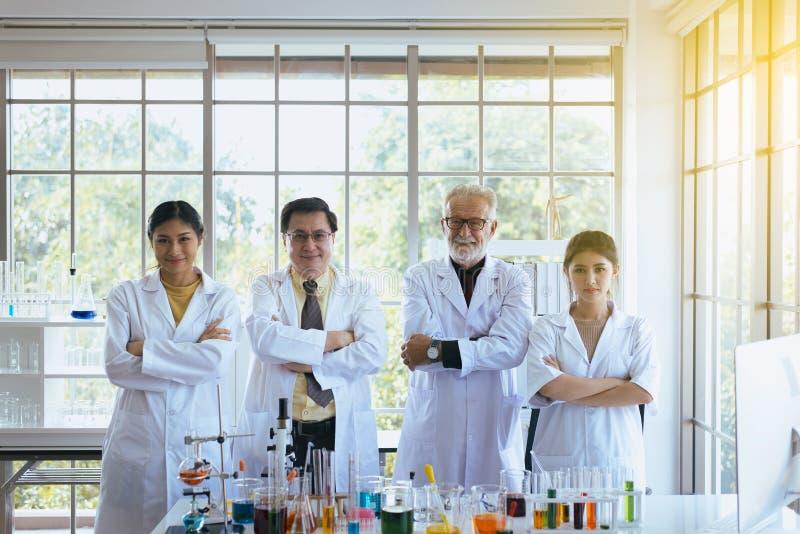 Stående forskare och arga armar, grupp av mångfaldfolkteamwork i laboratorium, framgång- och resercharbete royaltyfri fotografi