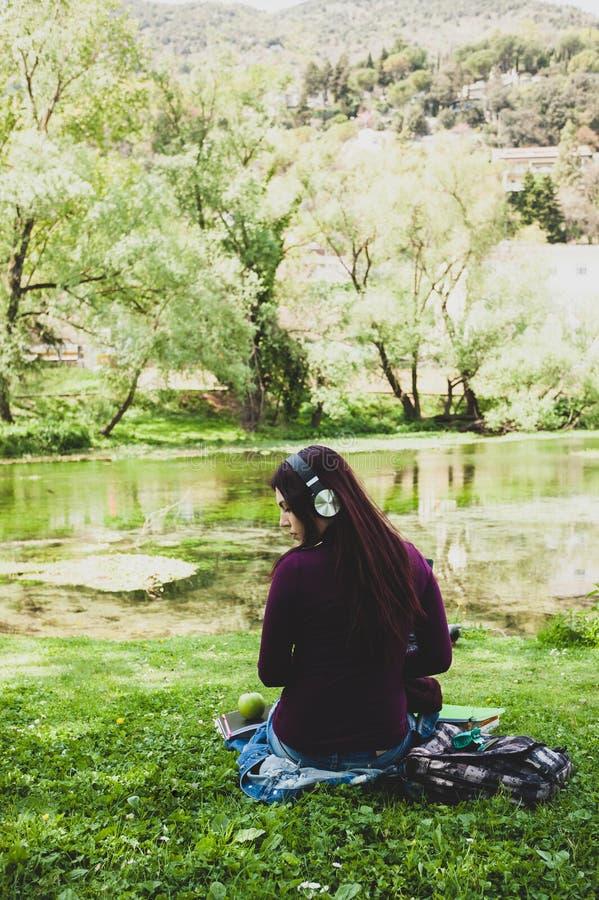 Stående från baksida av gullig lyssnande musik för ung kvinna royaltyfri fotografi