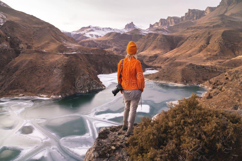 Stående från baksidan av flickahandelsresandefotografen i en orange tröja och hatt med en kamera i hand i arkivbilder