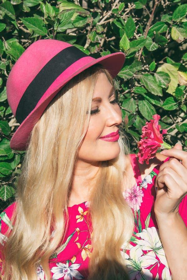 Stående Härlig blond flicka i en hatt Rymma blomman i hans hand på öppen luft Bak hennes gröna lövverk royaltyfri foto