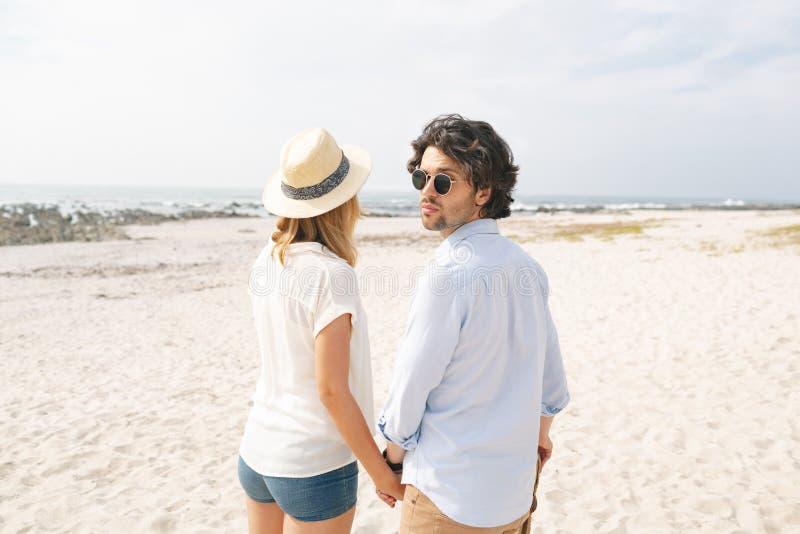 Stående hand för Caucasian par - i - hand på stranden fotografering för bildbyråer