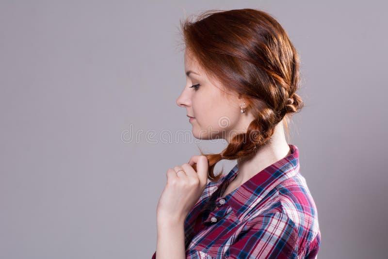 Stående i profil av en härlig rödhårig flicka med råttsvansar royaltyfri foto
