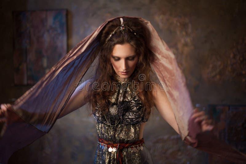 Stående i sjalen Stam- dansare, härlig kvinna i den etniska stilen på en texturerad bakgrund royaltyfri bild