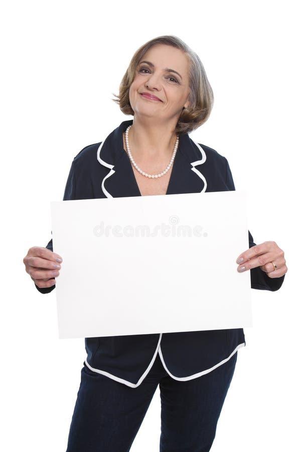 Stående: isolerad hög affärskvinna som rymmer ett vitt tecken för royaltyfri fotografi
