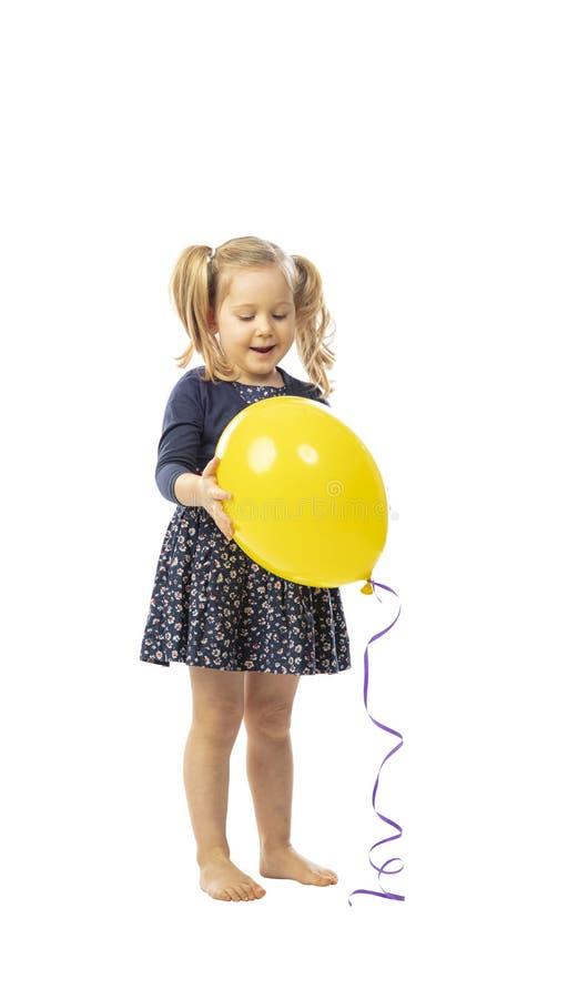 Stående liten flicka har en gul ballong royaltyfri foto