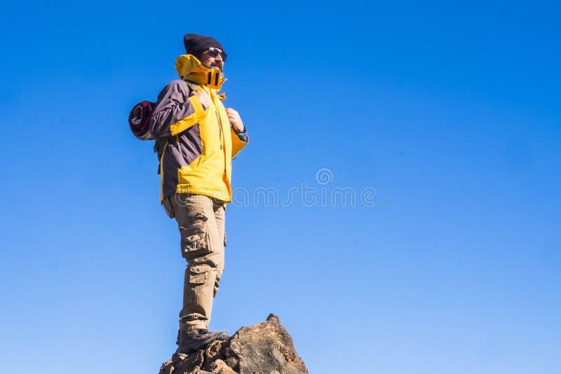 Stående lycklig man med ryggsäcken och fotvandrautrustning på överkanten av berget - begreppet av vandringen och loppet för folk  fotografering för bildbyråer