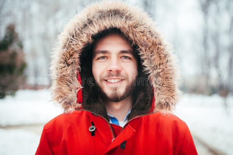 Stående närbild av klädd man för barn som en stylishly ler med ett iklätt skägg ett rött vinteromslag med en huv och en päls på h fotografering för bildbyråer