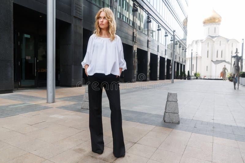 Stående oavkortad tillväxt för allvarlig blond kvinna på gatastad arkivbilder