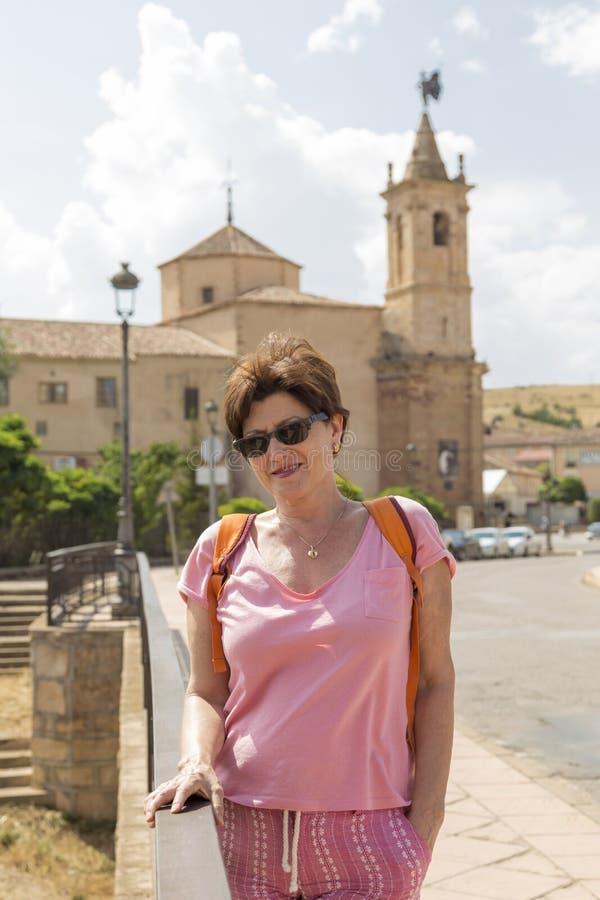 Stående på semester, i bakgrunden en kyrka, Molina de Aragà ³ n, Guadalajara, Spanien arkivbild