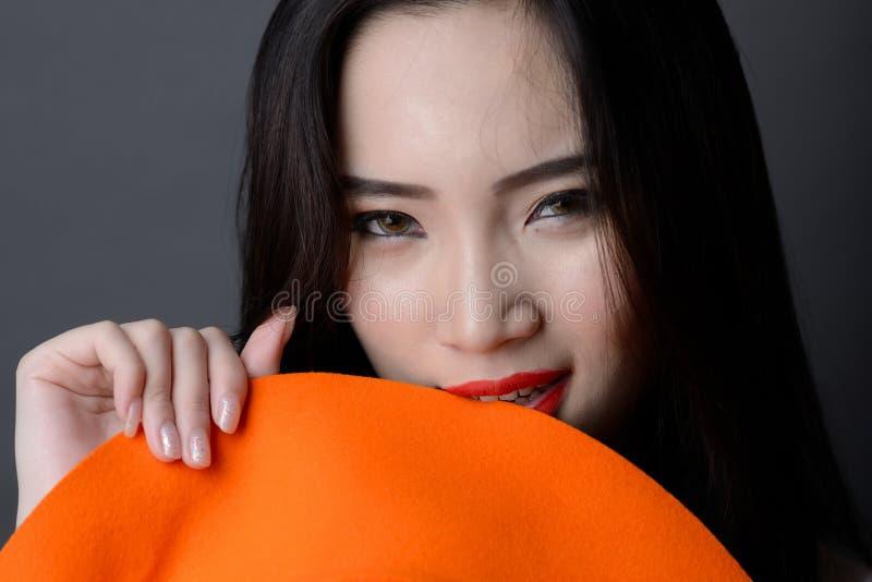 Stående som är nära upp av härlig asiatisk röd tugga a för kantkvinnamodell arkivfoto