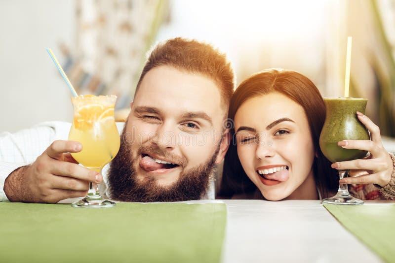 Stående som ler förälskade dricka coctailar för par arkivbild