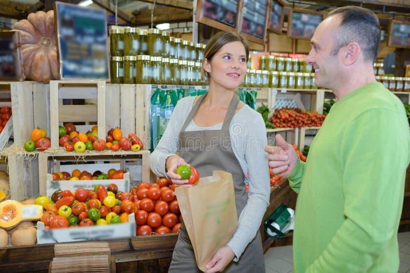 Stående som ler säljare med frukter och veggies i livsmedelsbutik arkivfoto