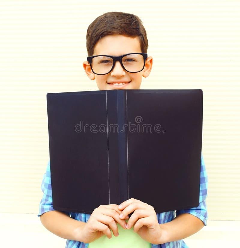 stående som ler tonåringpojken i glasögon med mappen eller boken arkivfoto