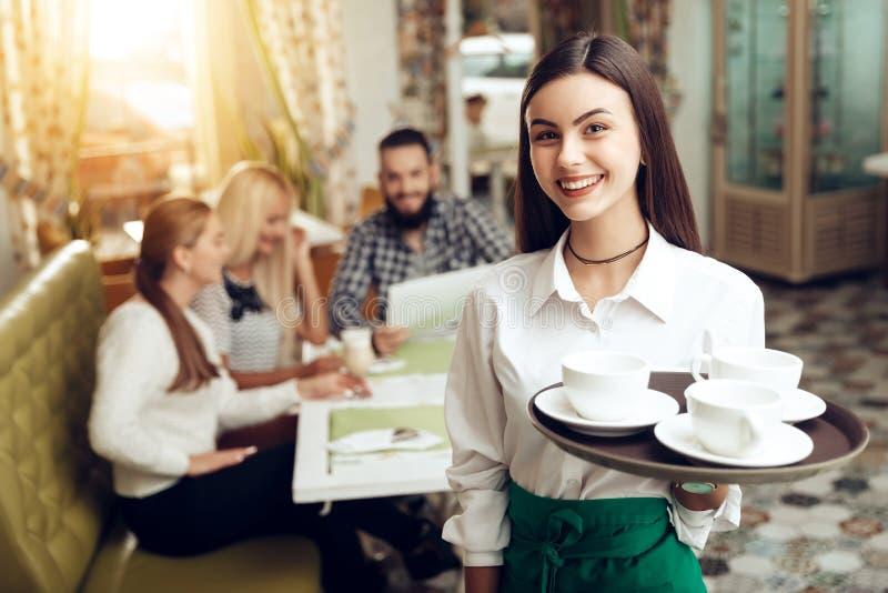 Stående som ler ungt servitrisanseende i kafé royaltyfria bilder
